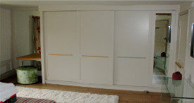 Bespoke sliding door wardrobe in painted tulipwood and oak interior