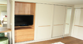 Fitted sliding door wardrobe in painted tulipwood and oak interior